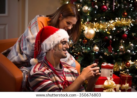 Young couple using smart phone while sitting in front of the Christmas tree  - stock photo