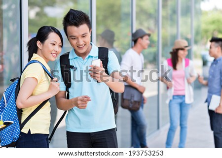 Young couple using smartphone, while their friends talking in the background - stock photo