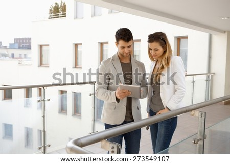 Young couple using tablet in balcony, smiling. - stock photo