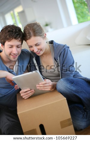 Young couple using tablet to find transport company - stock photo