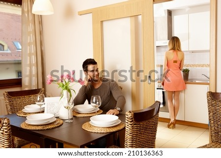 Young couple waiting for dinner guests at home, woman in kitchen cooking. - stock photo