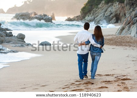 Young couple walking along lonely beach at sunset. - stock photo