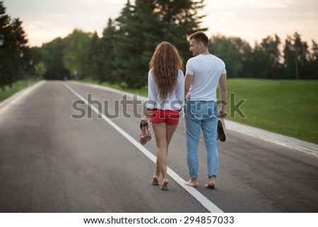 Young couple walking along the road in sunset without shoes. Man and woman enjoying day off and carrying their shoes. - stock photo