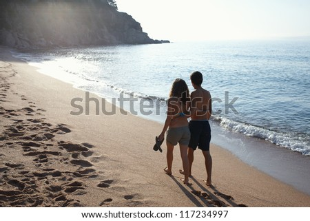 Young couple walking by the beach - stock photo