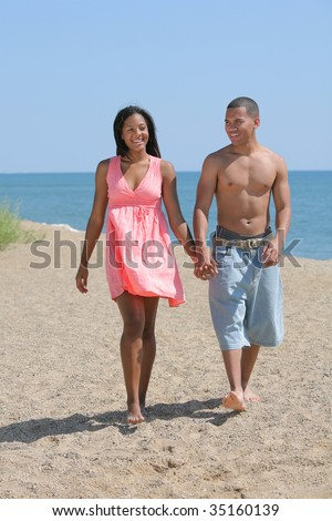 Young Couple Walking by the Beach under Summer Sunlight - stock photo