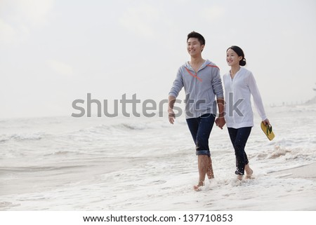 Young couple walking by the waters edge on the beach, China - stock photo