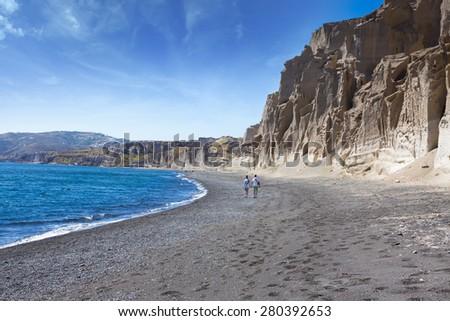 young couple walking coast on the island of Santorini, Greece.Vlichada beach - stock photo