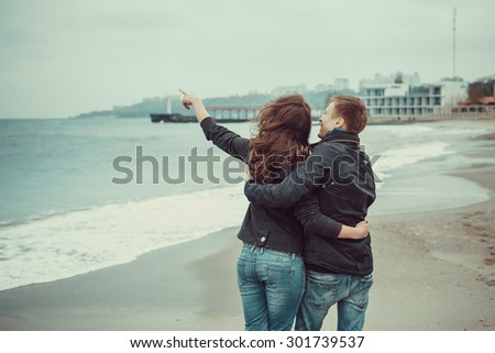 Young couple walking in a good mood on the beach on a cool windy day - stock photo