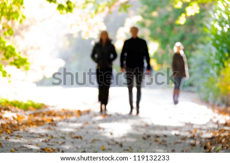 Young couple walking in the park. Blurred motion. - stock photo