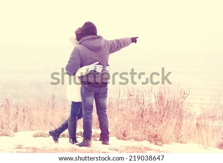 Young couple walking in winter park - stock photo
