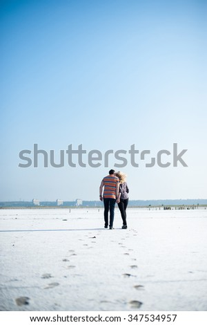 Young couple walking on a sandy beach - stock photo