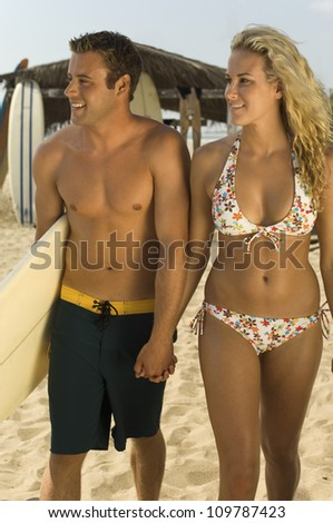 Young couple walking on beach holding hands with man carrying surfboard - stock photo