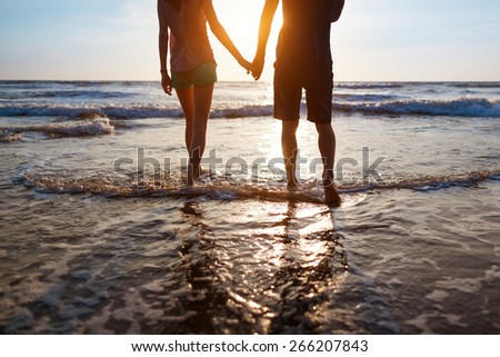 Young couple walking on the beach at sunset - stock photo