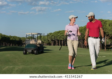 young couple walking to next hole on golf course. man carrying golf bag - stock photo
