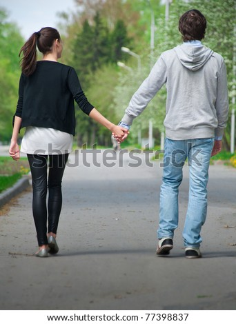 Young couple walking together hand by hand  in park, rear view - stock photo