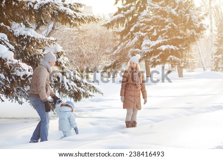 Young couple walking with a child in the woods  - stock photo