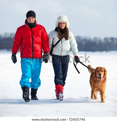 Young couple walking with dog. - stock photo