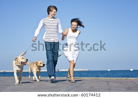 Young Couple Walking with Dogs - stock photo