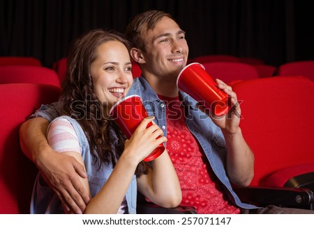 Young couple watching a film at the cinema - stock photo