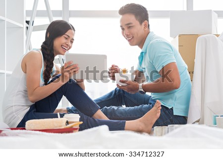 Young couple watching something funny on digital tablet when having lunch in new house - stock photo