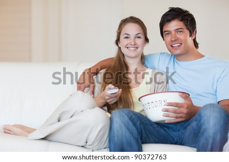 Young couple watching television while eating popcorn in their living room - stock photo