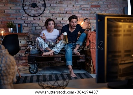 Young couple watching tv at home, jittering. - stock photo