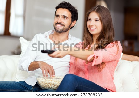 Young couple watching tv on a sofa  - stock photo