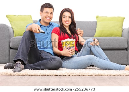 Young couple watching TV seated on the floor isolated on white background - stock photo