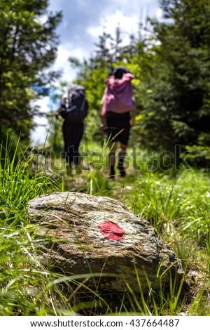 Young couple while hiking in a romanian forest on their vacation right near the Fogaras mountains, following the red blaze painted recently. - stock photo