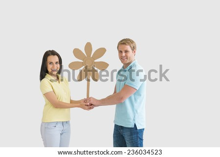 Young couple with a cardboard flower - stock photo