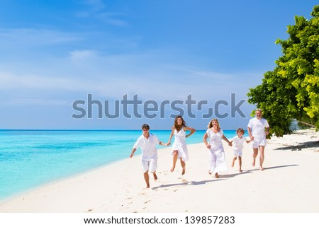 Young couple with a child and grandparents running on a beach - stock photo
