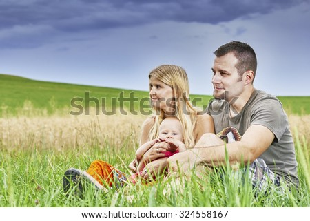 Young couple with a child sitting in the grass with sky in the background - stock photo
