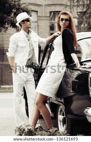 Young couple with a classic car - stock photo