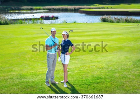 Young couple with a golf club on lawn - stock photo