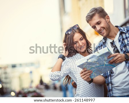 Young couple with a map in the city - stock photo