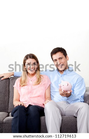 Young couple with a piggy bank sitting on couch - stock photo