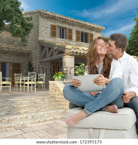 Young couple with a tablet  by a magnificent house - stock photo