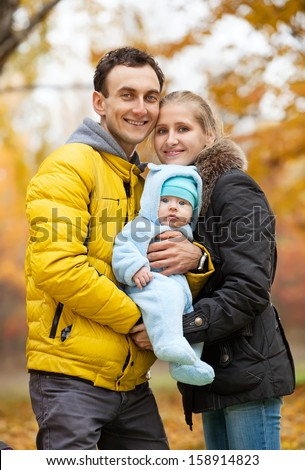 Young couple with baby boy on looking at camera in autumn park - stock photo