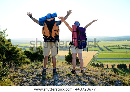 young couple with backpack on adventure mountain trek admiring a beautiful sunset landscape - stock photo