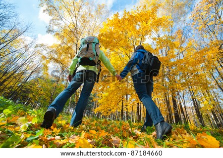 Young couple with backpacks in the park. Fall. - stock photo