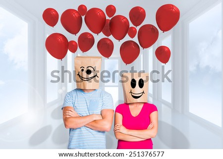 Young couple with bags over heads against bright white hall with windows - stock photo