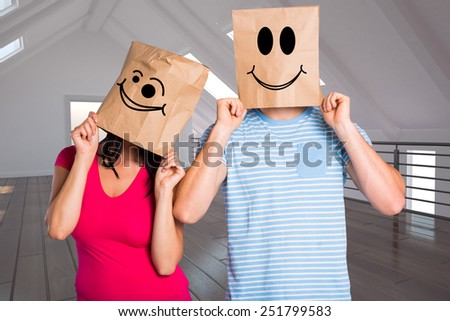 Young couple with bags over heads against white room with open door - stock photo