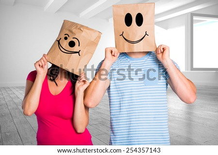 Young couple with bags over heads against white room with windows - stock photo