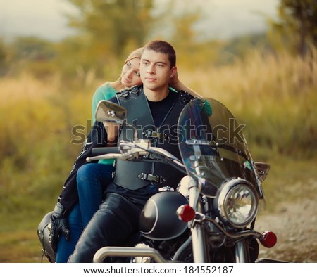 Young couple with beautiful bike on road. - stock photo