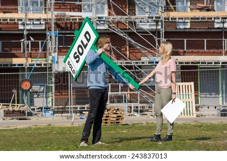 Young couple with blueprint is happy in front of their new built house they just bought - stock photo
