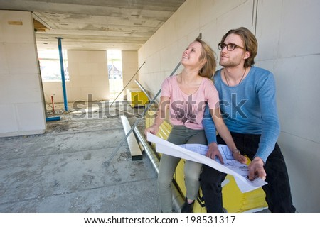 Young couple with blueprint is looking in the living room how their new home is being built - stock photo