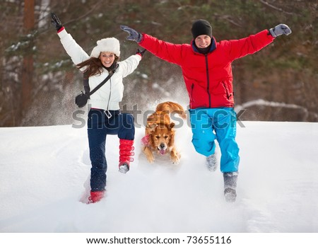 Young couple with dog winter outdoors fun. - stock photo