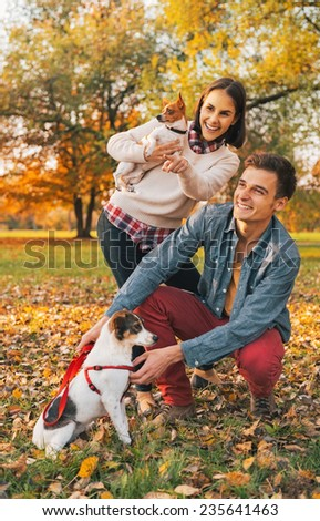 Young couple with dogs pointing on copy space outdoors in autumn park - stock photo