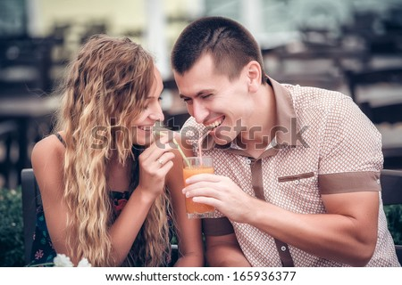 young couple with drinks in cafe outdoor, summer day - stock photo