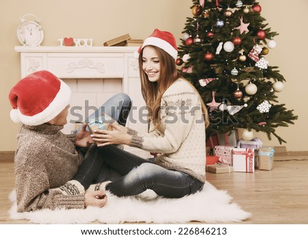 Young couple with gifts, sitting on carpet, at home - stock photo